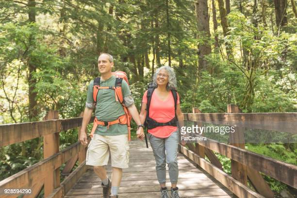 senior couple hiking in the forest - hot older women stock pictures, royalty-free photos & images