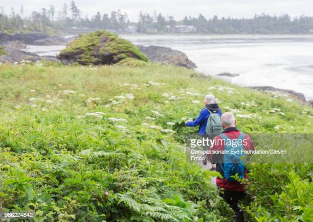 senior couple hiking on path by ocean - vancouver island stockfoto's en -beelden