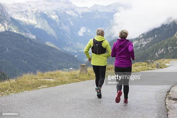 senior couple hiking on road - black pants fotografías e imágenes de stock