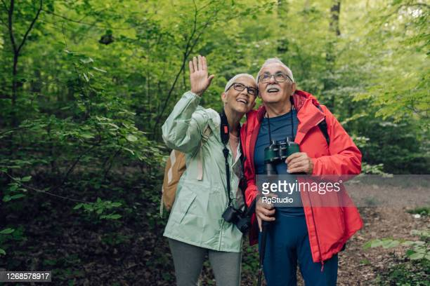 senior couple hiking through the forest, watching birds and enjoying - binoculars stock pictures, royalty-free photos & images