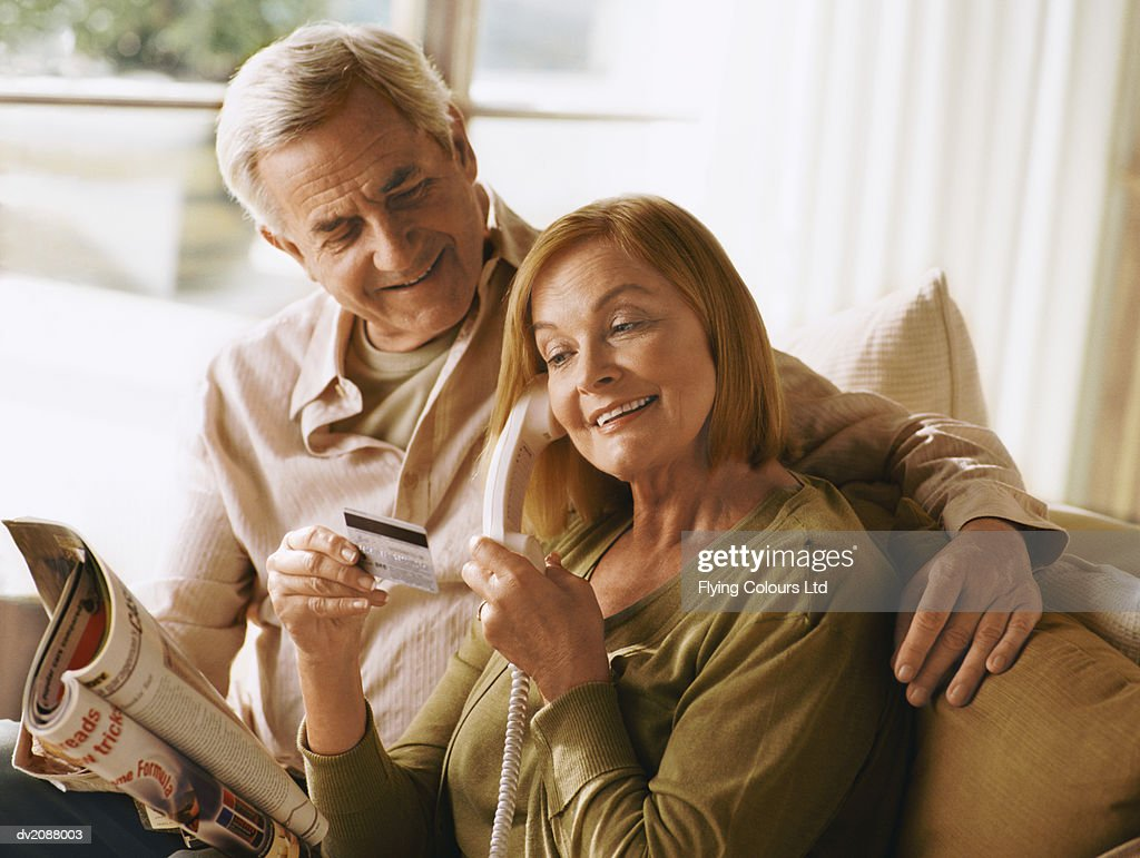 Senior Couple Holding a Bank Card and Ordering Over the Phone From a Magazine : Stock Photo