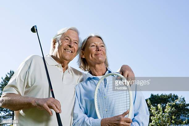 A senior couple holding a golf club and a tennis racket