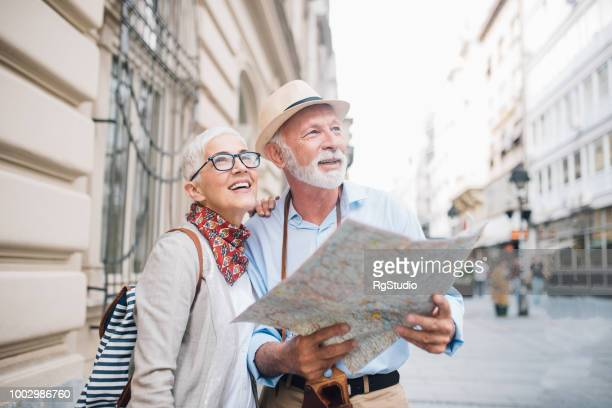 senior couple holding a map and looking at distance - tourist attraction stock pictures, royalty-free photos & images