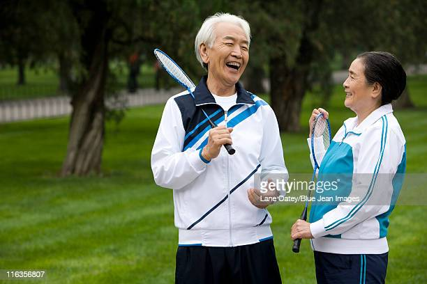 Senior Couple Holding Badminton Rackets in a Park