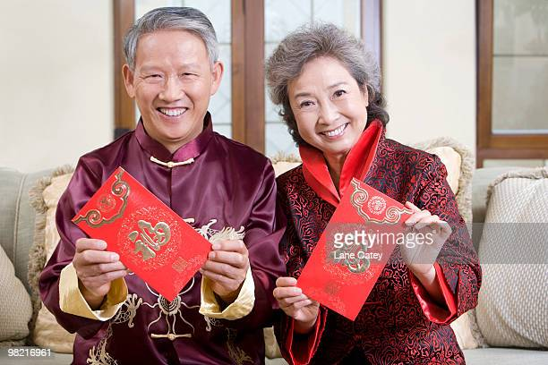 senior couple holding chinese new year red envelop - 63 year old female stock pictures, royalty-free photos & images