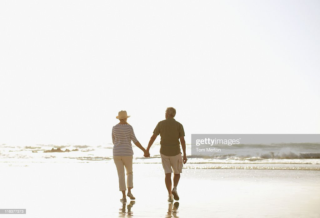 Senior couple holding hands and walking on beach : Stock Photo
