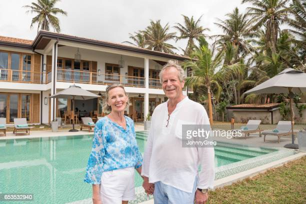 Senior couple holding hands by swimming pool on vacation