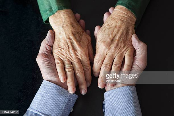 Senior couple holding hands, close-up