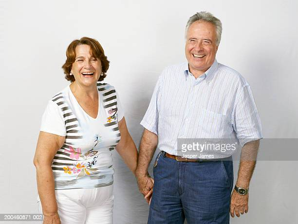 Senior couple, holding hands, laughing, portrait