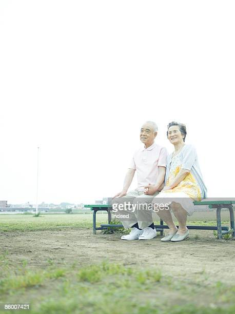 Senior couple holding hands on bench