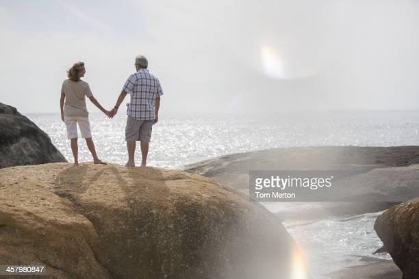 Senior couple holding hands on rocks at beach