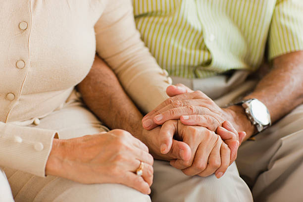 senior couple holding hands on sofa - asian old couple stock pictures, royalty-free photos & images