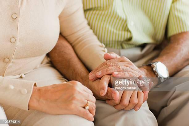 Senior couple holding hands on sofa
