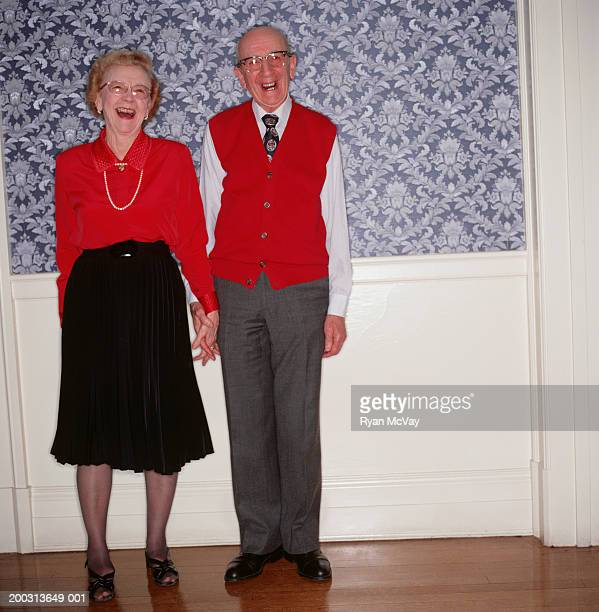 Senior couple holding hands, side by side indoors, portrait
