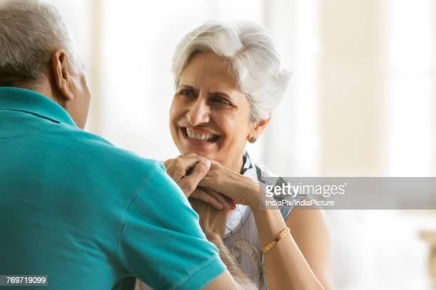 senior couple holding hands sitting at table - indian couples stock pictures, royalty-free photos & images