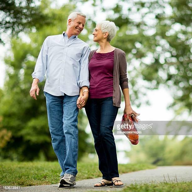 Ältere paar Hände halten zu Fuß im Park