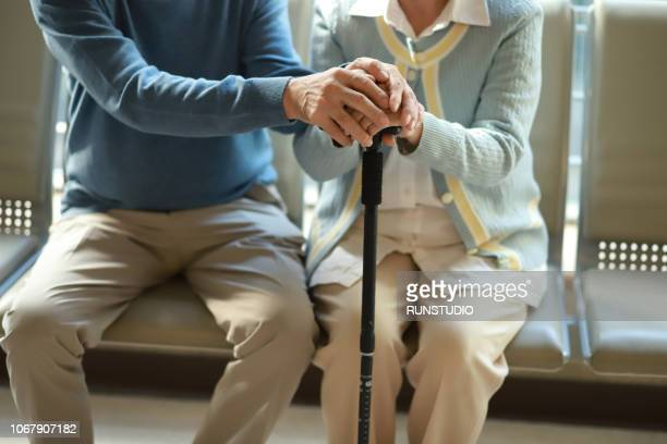 senior couple holding hands with walking cane - disability stock pictures, royalty-free photos & images