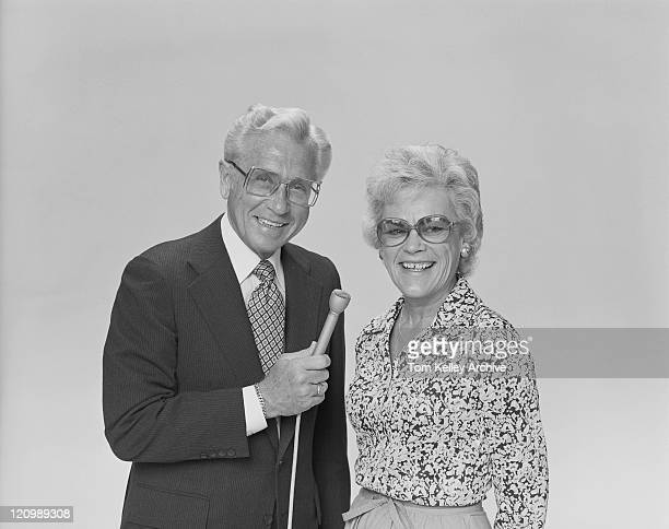 couple Senior tenant un microphone, souriant, portrait