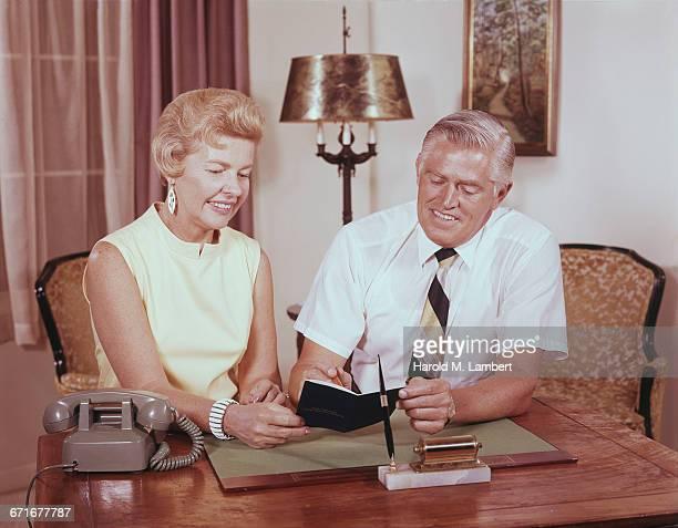 senior couple holding passbook and smiling  - {{ contactusnotification.cta }} stockfoto's en -beelden
