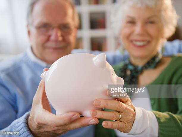 Senior couple holding piggy bank