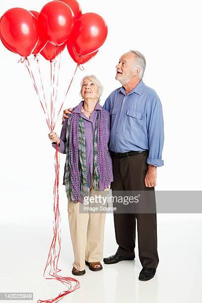 Pareja Senior sosteniendo rojo globos contra fondo blanco