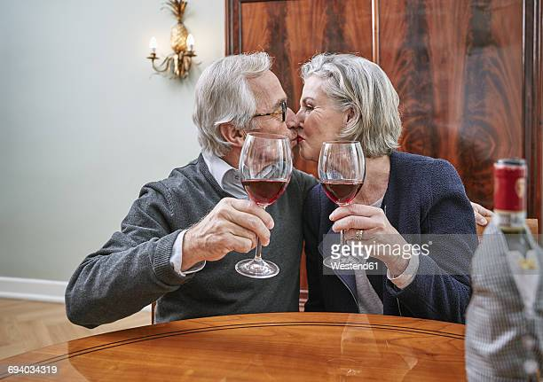 Senior couple holding red wine glasses kissing