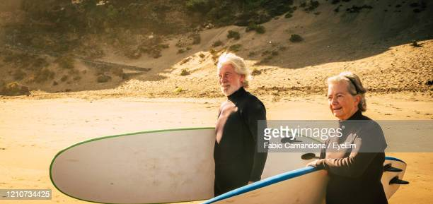 senior couple holding surfboards at beach - water sport stock pictures, royalty-free photos & images