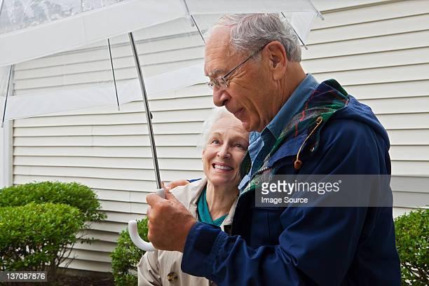 Senior couple holding umbrella outside