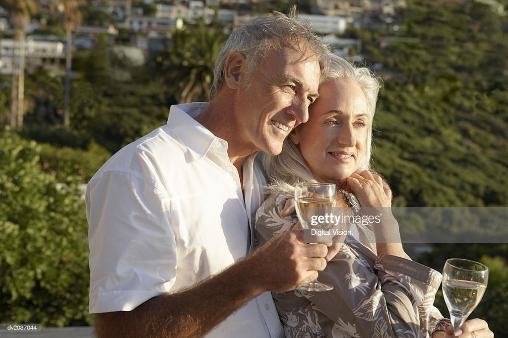 Senior Couple Holding Wine Glasses and Looking Away : Stock Photo
