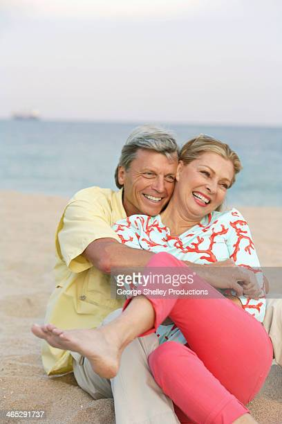 Senior couple hugging and laughing on the beach