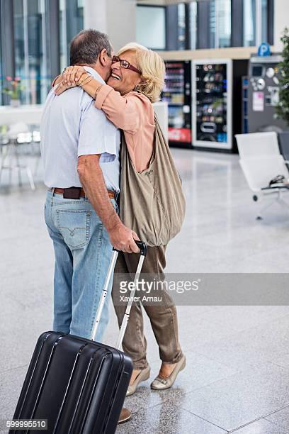 Senior couple hugging in airport