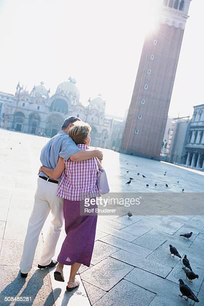 Senior couple hugging in St. Mark's Square, Venice, Veneto, Italy