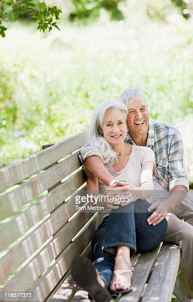 Altes Paar umarmen auf der Bank