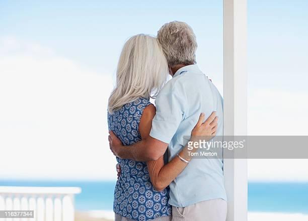 Altes Paar umarmen auf der Terrasse und Blick auf das Meer