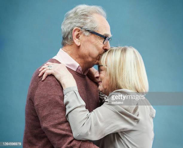 senior couple hugging - stellalevi stock pictures, royalty-free photos & images