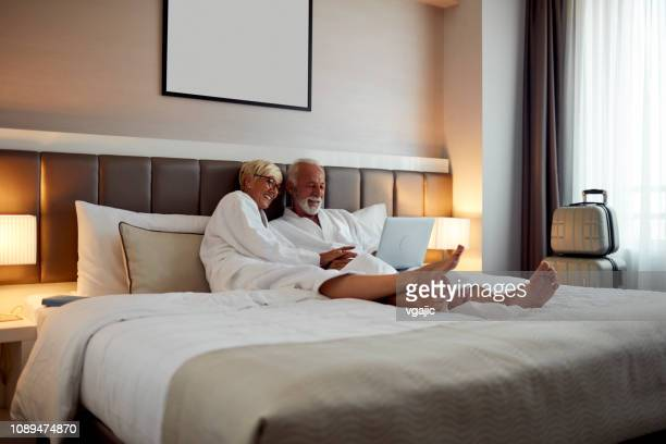 senior couple in a hotel - double bed stock pictures, royalty-free photos & images