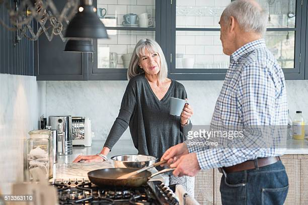 senior couple in a kitchen making dinner and talking - wife stock pictures, royalty-free photos & images