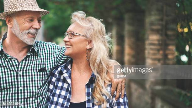 senior couple in a relaxing walk. - gray hat stock pictures, royalty-free photos & images