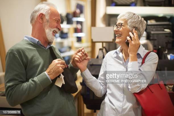 couple de personnes âgées dans un magasin de shopping pour un sac ensemble - crossbody bag photos et images de collection