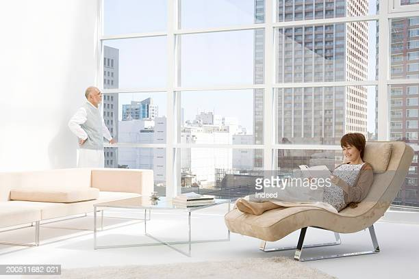senior couple in apartment, woman on chaise longue, man by window - chaise longue stock photos and pictures