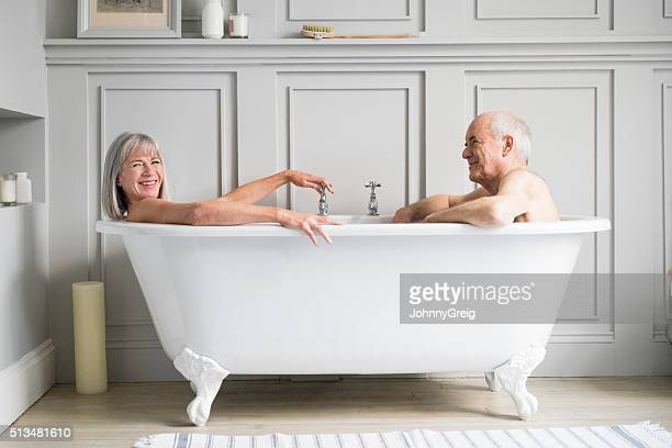 senior couple in bath together smiling - couples showering stock pictures, royalty-free photos & images