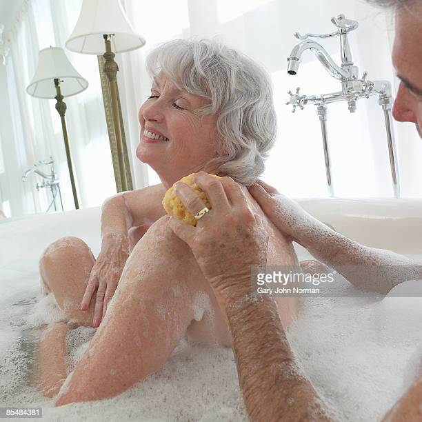 Senior couple in bath together washing women back