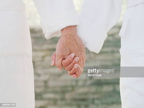 Senior couple in bathrobes holding hands