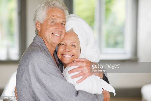 senior couple in bathrobes hugging - wrapped in a towel stock pictures, royalty-free photos & images
