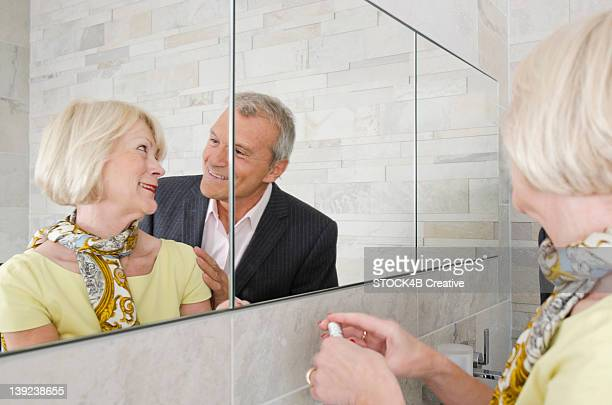 Senior couple in bathroom preparing to going out