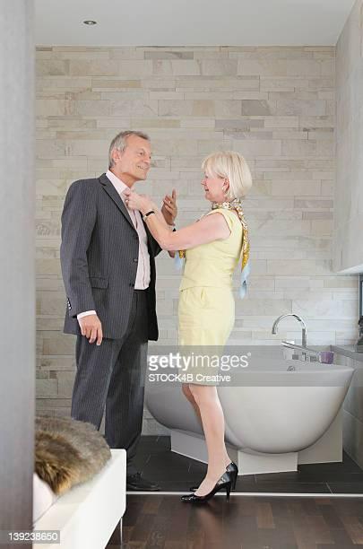 Senior couple in bathroom putting on evening wear