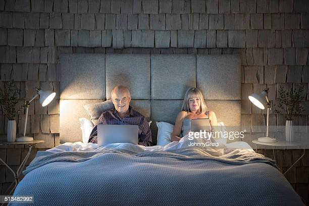 senior couple in bed at night with laptop and tablet - lamp stock photos and pictures