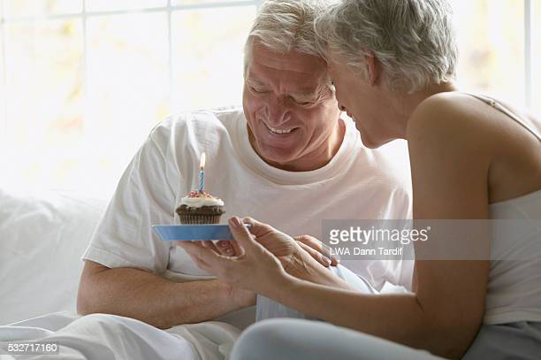 Senior Couple in Bed with Birthday Cake