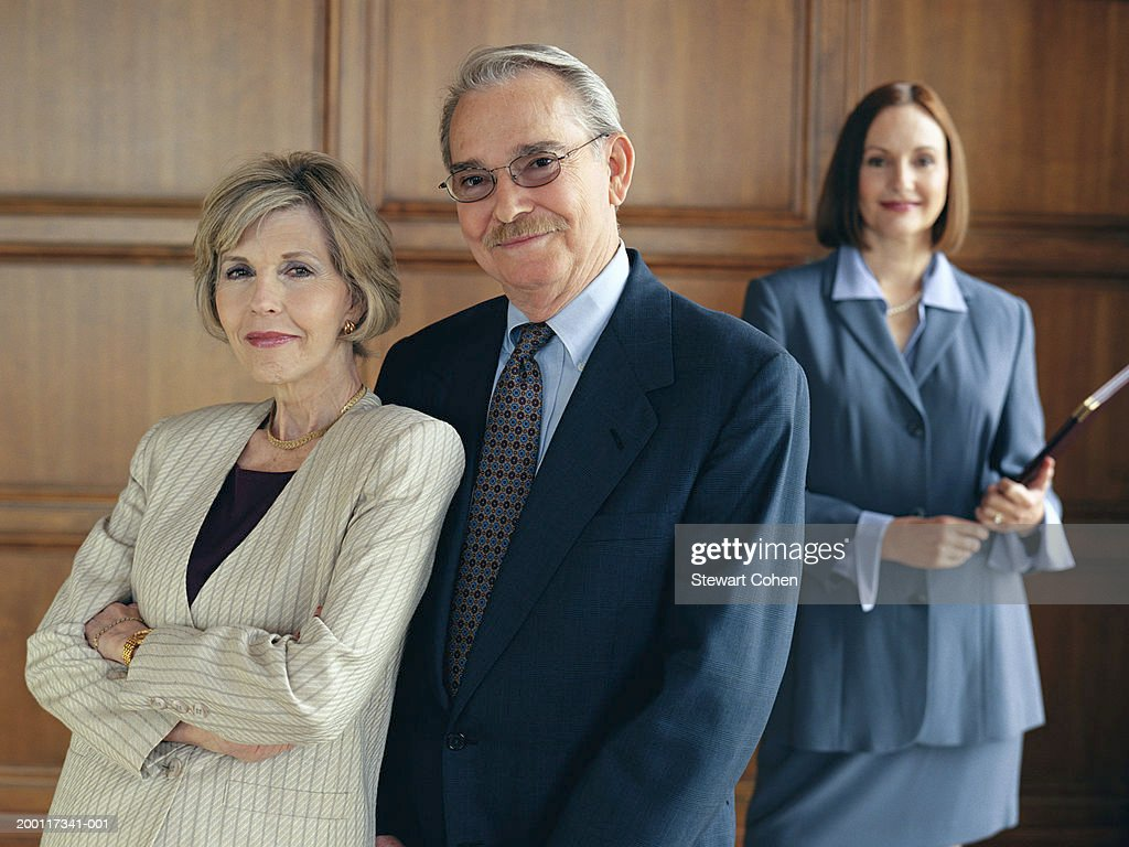 senior couple in business attire standing in front of business woman