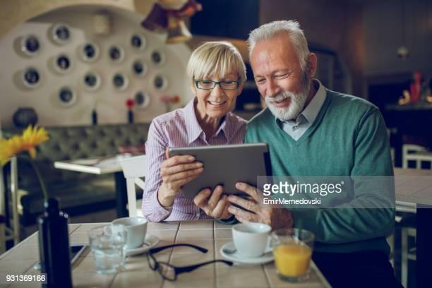 Couple de personnes âgées dans le café à l'aide de tablette numérique